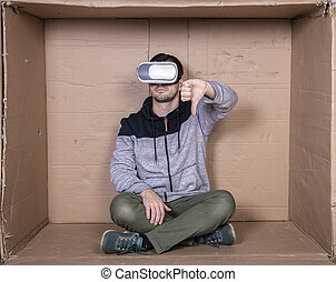 man with glasses for virtual reality, sitting in a cardboard room and showing thumbs down