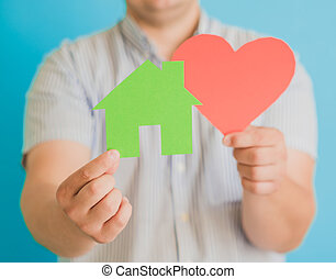 heart and a small house in the hands of