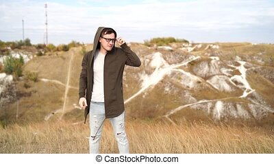 Man with glasses in jeans, t-shirt and cape stands in hilly ...