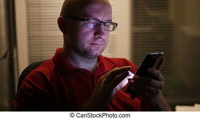 man with glasses sitting in an office using a smartphone