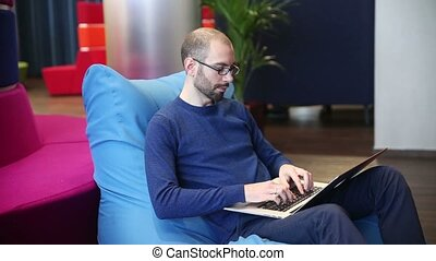 Man with glasses working on laptop