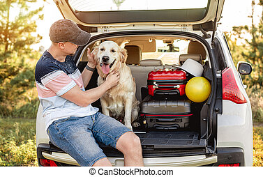 Man with golden retriever in car trunk