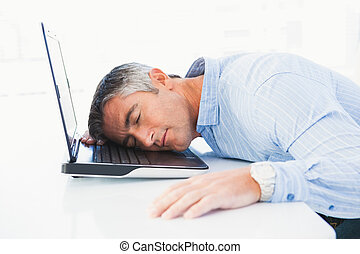 Man with grey hair sleeping on his laptop in his office