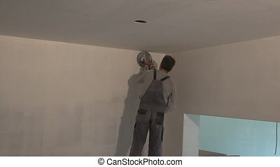 Man with grinder machine polishing wall at new apartment
