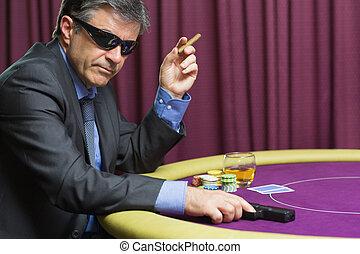 Man with gun at poker table