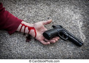 Man with gun in hand bloodstained lies dead in the asphalt murder victim