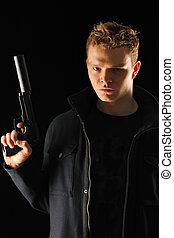 Man with gun - Man holding gun with silencer over black