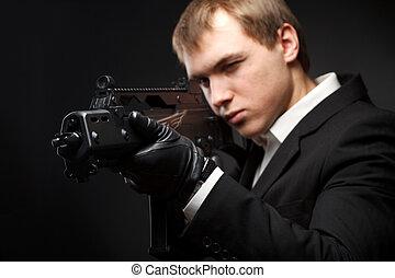 Man with gun over gradient gray. Focused on gun