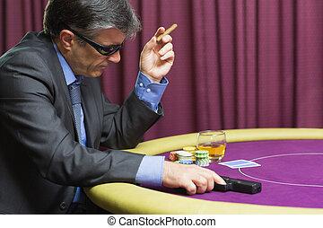 Man with gun sitting at poker table