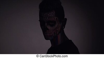 Man with Halloween skull make up in studio. Light and shadow...