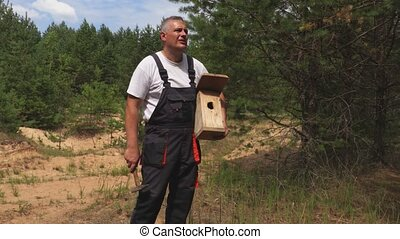 Man with hammer and bird box