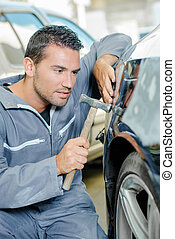 man with hammer tapping car