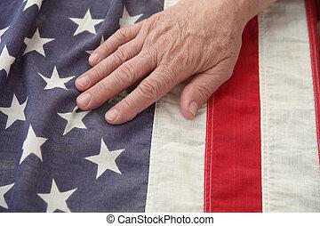 man with hand on USA flag