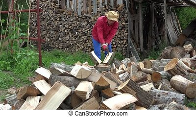 man with hat chop firewood axe for winter. Work in country. 4K