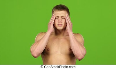 Man with headache is massages his temples hands, green...