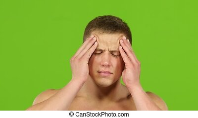 Man with headache is massages temples hands, green screen....