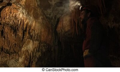 Man with headlamp inside cave in the dark