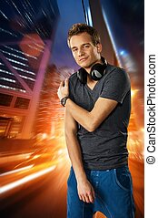 Man with headphones against night city background