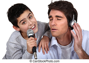 Man with headphones and little boy singing in a microphone