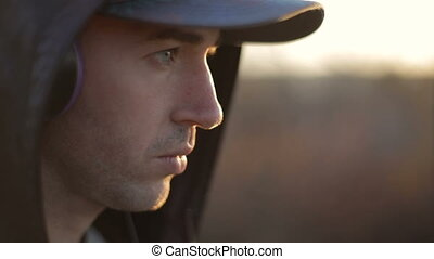 Thinking man wears headphones, cap and hood against sunset outdoors, dilemma problem thinking concept