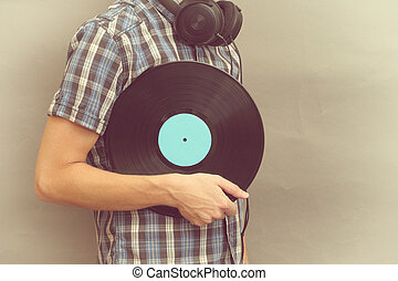 Man with headphones holds vinyl record in his hand