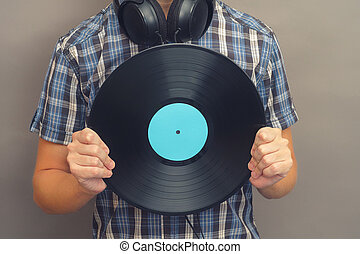Man with headphones holds vinyl record in his hands