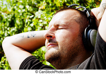 man with headphones listening music in park
