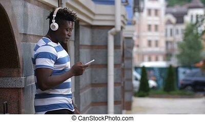 Man with headphones listening music on smart phone - Stylish...