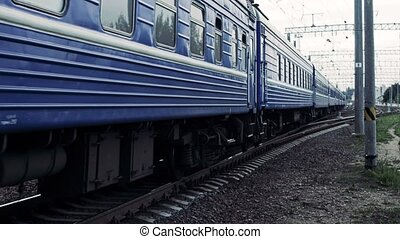 Man with headphones passes through a rairoad in front of the moving train, life threatening