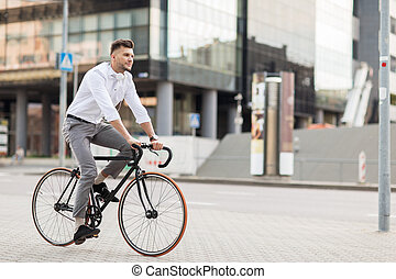 man with headphones riding bicycle on city street -...