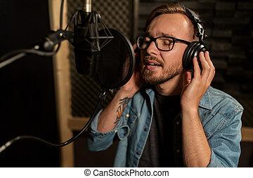 man with headphones singing at recording studio - music,...