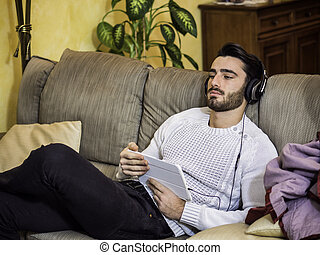 Man with headphones using tablet PC