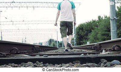 man with headphones walks along the railway, dangerous for life