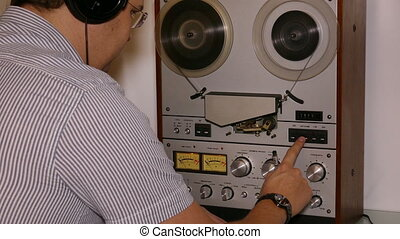 man with headphones working with reel tape recorder