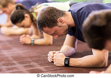 fitness, sport, exercising, people and healthy lifestyle concept - man with heart-rate tracker at group training doing plank exercise in gym
