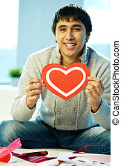 Man with heart - Portrait of happy man holding red paper...