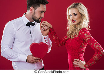 Man with heartshape box holding woman's hand