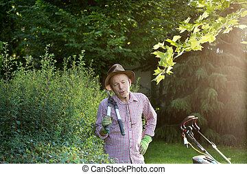Man with hedge scissors in garden