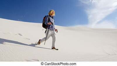 Man with hiking pole climbing down the sand dunes 4k - Man...