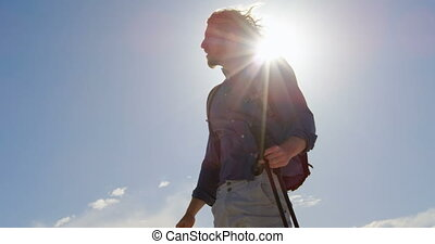 Man with hiking pole shielding his eyes 4k - Man with hiking...