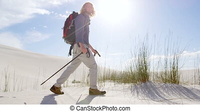 Man with hiking pole walking in the desert 4k