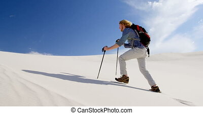 Man with hiking pole walking on the sand dunes 4k