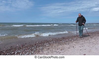 Man with hiking sticks keep hands up at beach near sea