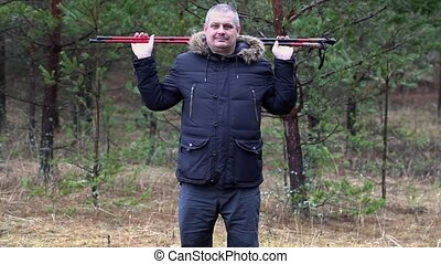 Man with hiking sticks warm up in forest