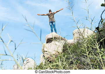 man with his arms in the air on the top of a rock