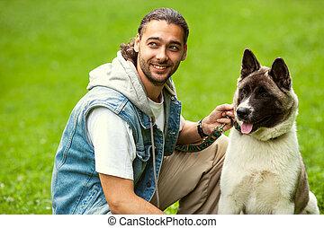 man with his dog breed Aki