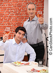 Man with his grandson eating in a restaurant