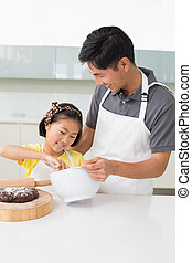 Man with his young daughter preparing food in kitchen