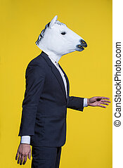 man with horse mask on yellow background
