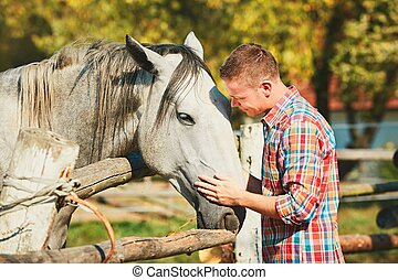 Man with horse - Young man stroking horse at the farm in...
